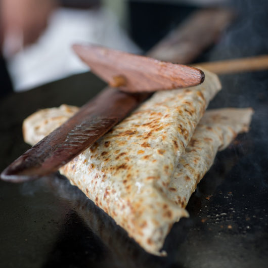 Folded crepe on a hot griddle being pressed with a wooden crepe trowel and scraper.